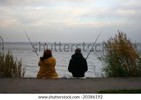 Two people are fishing - stock photo