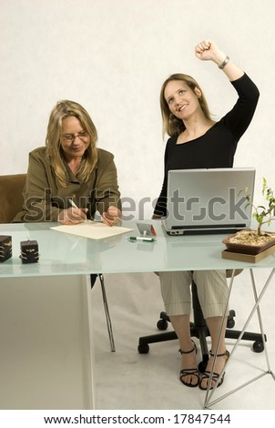 Two people are sitting together in a room at a table. The older woman is writing on a piece of paper and the younger woman is looking at the ceiling and has her hand raised. - stock photo