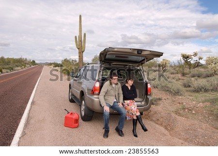 Two people are stranded on the side of a remote desert road out of gas. - stock photo