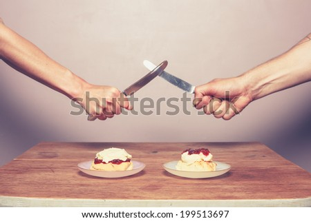 Two people at table are fighting over how to make the perfect cream tea - stock photo