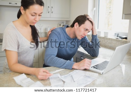 Two people calculating finances and using the laptop - stock photo