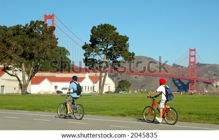 Two people cycling in the Presidio near the Golden Gate Bridge in San Francisco - stock photo