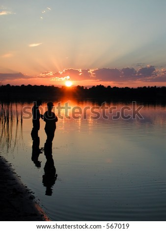 Two people evening fishing on the river - stock photo