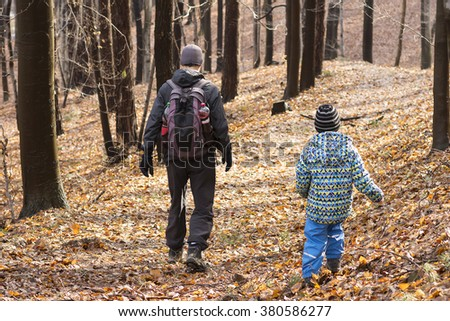 Two people, father and son, walking or hiking in autumn forest, back view.  - stock photo