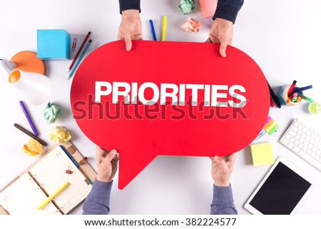 Two people holding speech bubble with PRIORITIES concept - stock photo