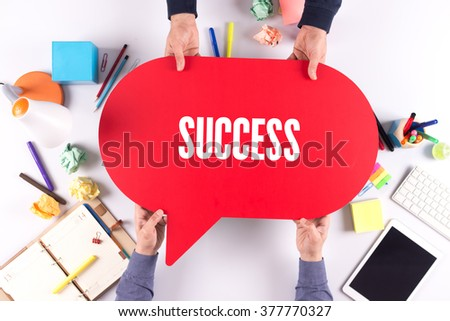 Two people holding speech bubble with SUCCESS concept - stock photo