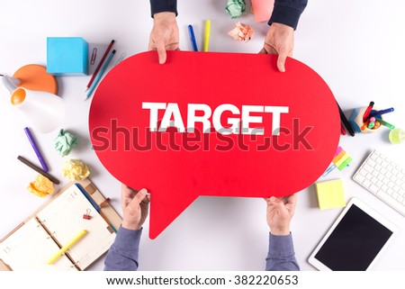 Two people holding speech bubble with TARGET concept - stock photo