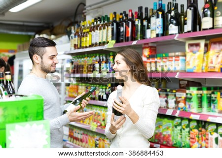 Two people in s supermarket alcohol section. Man gives woman an advice which wine to choose - stock photo