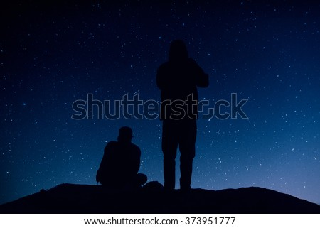 Two people look at the night sky full of stars and wait the dawn.  Black silhouettes on a dark background of the sky. - stock photo