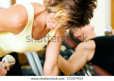 Two people (mature female / young male in the background) training with dumbbells in a gym - stock photo