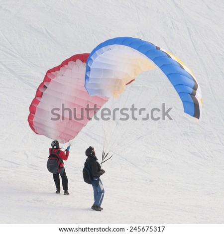 Two people on speed flying in winter Carpathian Mountains - stock photo