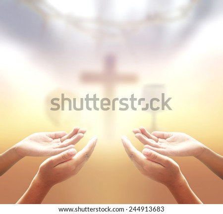 Two people open empty hands with palms up, over blurred crown of thorns and the cross with glass of wine and Loaf of bread in eucharist of christian. - stock photo