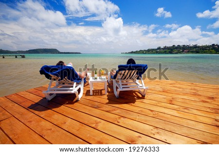 Two people relaxing on deck by the water - stock photo