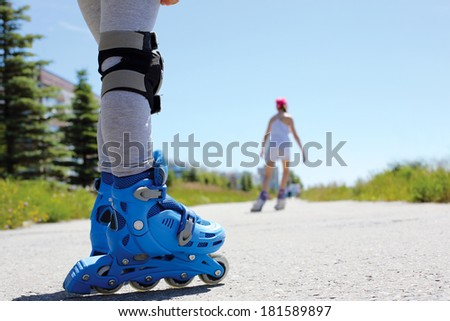 two people rollerblade on the street in the summer - stock photo