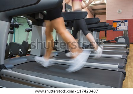 Two people running on treadmills in the gym side by side - stock photo