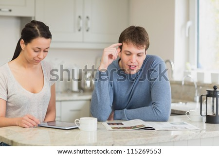 Two people sitting in a kitchen while they are talking and reading and drinking coffee - stock photo