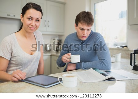 Two people sitting in the kitchen reading news and drinking coffee - stock photo