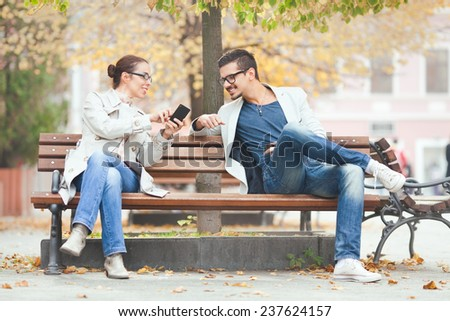 Two people sitting on a bench using mobile phone - stock photo