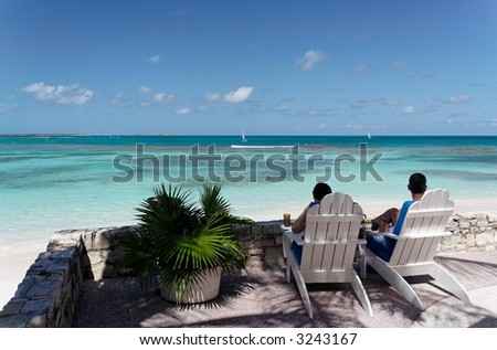 Two people sitting on canvas chairs at a beautiful caribbean terrace - stock photo