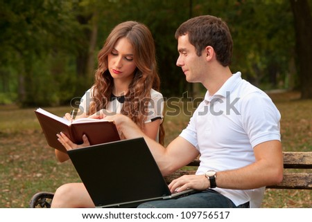 Two people solving business tasks in the park - stock photo
