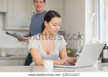 Two people spending time in the kitchen while using the laptop and reading a magazine - stock photo