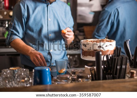 Two people standing behind the bar and prepare desserts - stock photo
