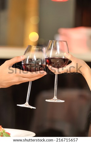 Two people toasting with wine glasses. young couple drinking red wine at restaurant - stock photo