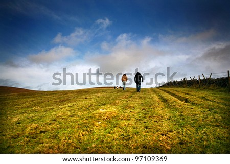 Two people walk in distance up a hill near Peak District in England - stock photo