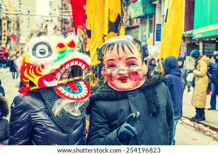 Two people wearing traditional Chinese masks, Big Head Doll and Lion, walking on street in Chinatown, Downtown of Manhattan, New York, celebrating Chinese New Year. Instagram filtered look. - stock photo