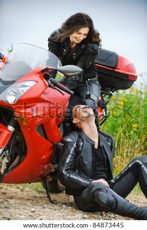 Two people: young beautiful woman sitting on motorbike and smiling man having rest. - stock photo