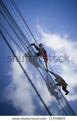 Two persons climbing building, connecting their hands - stock photo