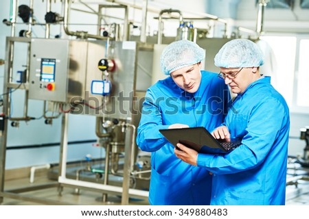 Two pharmaceutical technician male workers in water preparation production line hall at pharmacy industry manufacture factory using notebook computer - stock photo