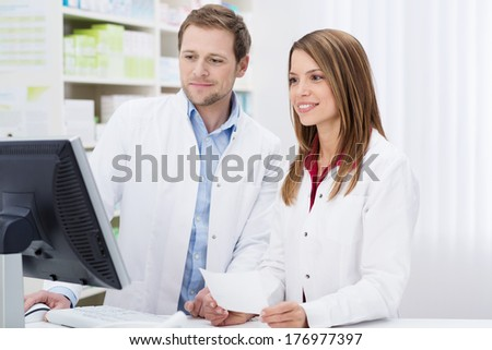 Two pharmacists fulfilling a prescription held in the young womans hand a they check information on the computer monitor together - stock photo