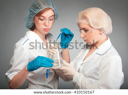 Two pharmacists in the lab to conduct experiments, chemical analysis. A doctor holds a flask with a substance, the second woman chemist adds reagent. - stock photo