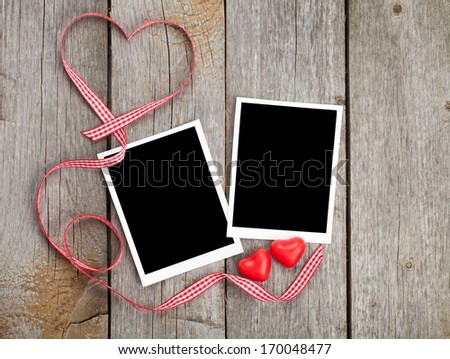 Two photo frames and small red candy heart on wooden background - stock photo