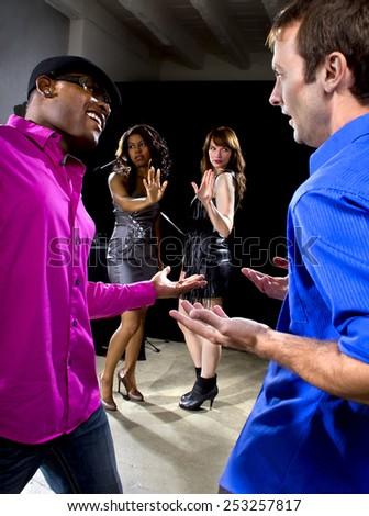 two pickup artists harrassing women at a nightclub - stock photo
