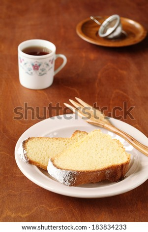 Two pieces of brazilian corn cake, on a plate, wooden fork and cup of coffee on a wooden table. - stock photo