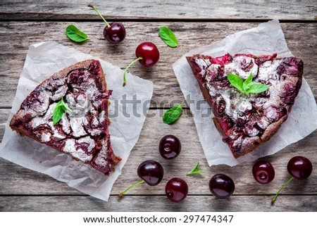 two pieces of chocolate cake Clafoutis with cherries on a wooden rustic table top view - stock photo