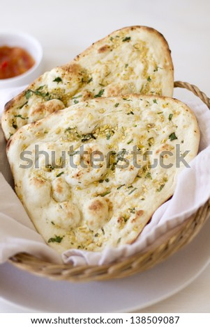 Two pieces of herbed garlic naan flatbread. - stock photo