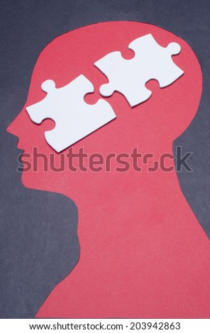 Two pieces of jigsaw puzzle pieces and black paper project as a outline of human head - stock photo