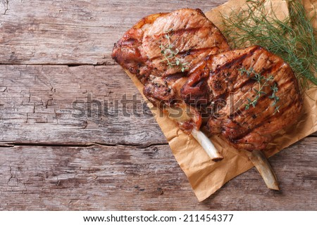 two pieces of of grilled pork with herbs on a paper on an old table top view horizontal close-up   - stock photo
