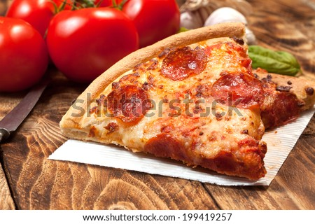 Two pieces of pizza with topping on a wooden table. - stock photo