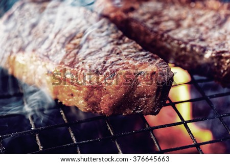 Two pieces of striploin steak on grill, outdoor picnic, toned - stock photo