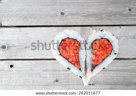 Two pieces of sushi forming the heart shape on a gray wooden background - stock photo