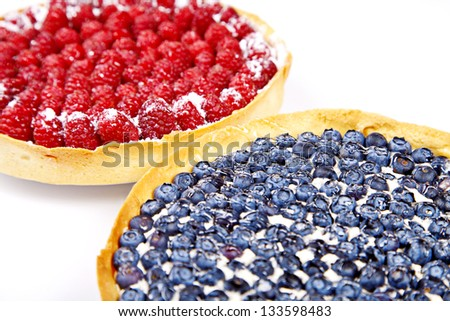 Two pies with blueberries and rasberries on white background - stock photo