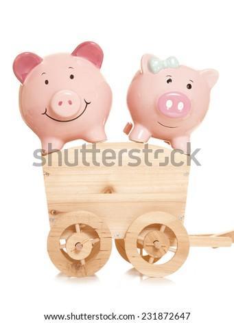 two piggybanks on a wooden cart cutout - stock photo