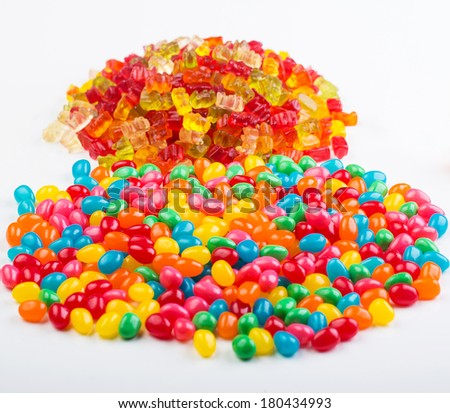 Two piles of candy featuring colorful jelly beans and gummy bears - stock photo