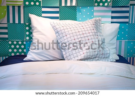 Two pillows on the bed with colored paper taped to the wall. - stock photo