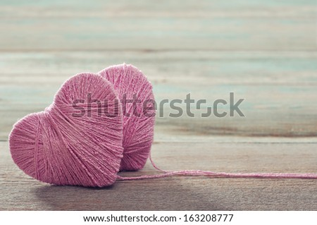 Two pink clews in shape of heart on vintage wooden background - stock photo