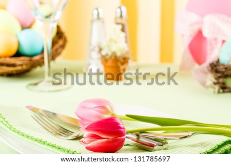 Two pink tulips grace a place setting on a colorful Easter table - stock photo
